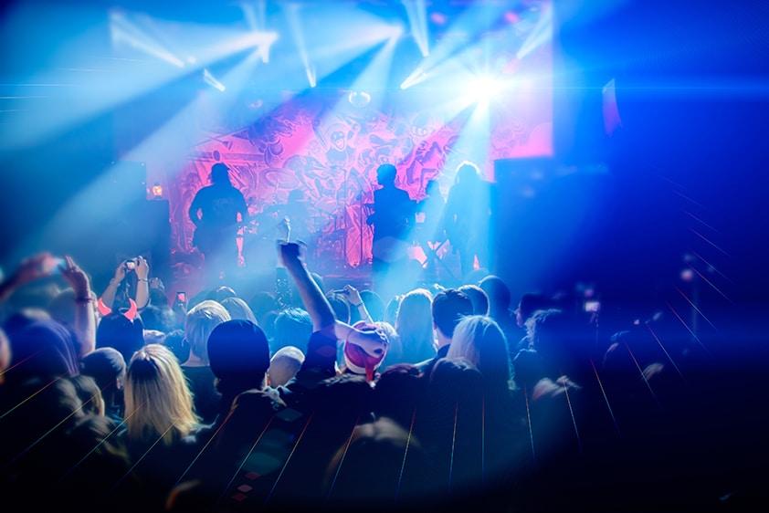Menschen tanzen, eine Band spielt auf der Bühne
