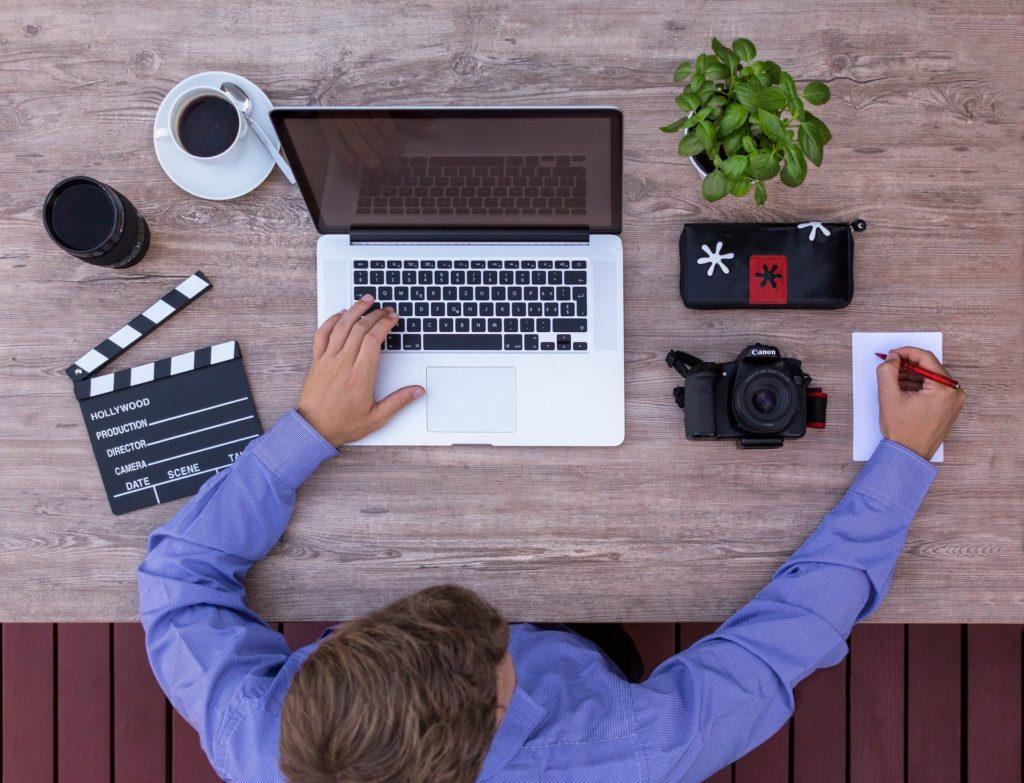 Mann an Schreibtisch Videoproduktion Laptop