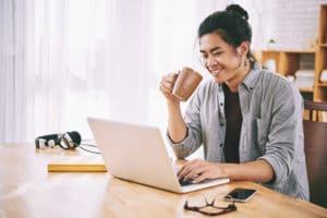 Joyful Asian man drinking coffee and browsing internet