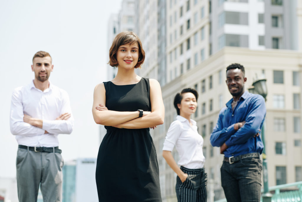 Smiling confident young Vietnamese business lady in black dress standing outdoors with coworkers and looking at camera