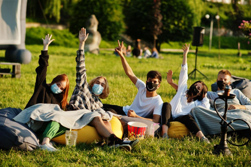 Young multi ethnic group of people watching movie at poof in open air cinema wear at mask during covid coronavirus quarantine.